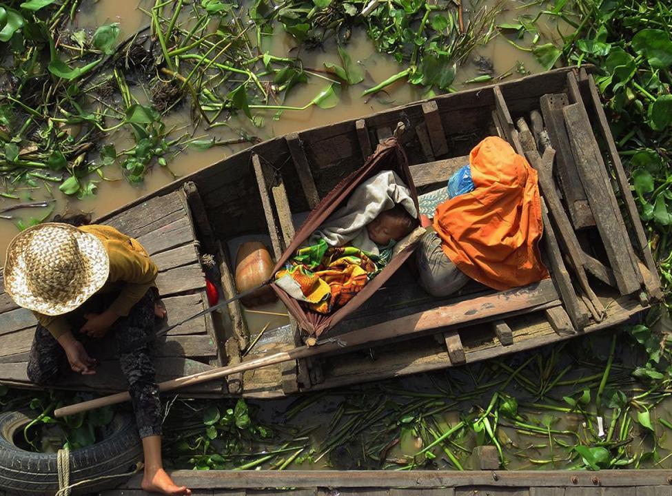 Bébé sieste dans une barque sur le Tonle Sap au Cambodge village flottant ©Brendan Abbenhuys